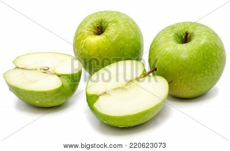 Sliced apple Granny Smith, two whole and two halves, isolated on white background