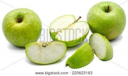 Sliced apple Granny Smith, two whole, three slices and one half, isolated on white background