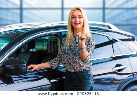 Young happy smiling blonde business woman driver holding auto keys in front of a luxury car