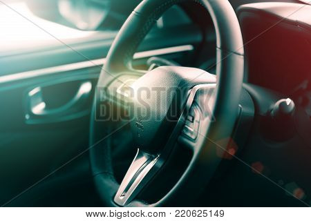 Closeup view of the steering wheel of a luxury car with selective focus effect