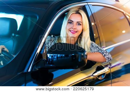 Happy smiling young woman in the modern luxury car
