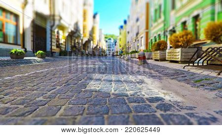 Old town street with stone pavement, blurred cars and pedestrians in vintage colors with selective focus effect