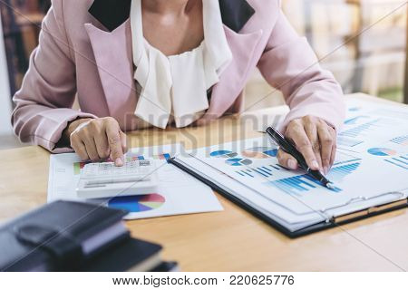 Female accountant calculations and analyzing financial graph data with calculator and laptop Business, Financing, Accounting, Doing finance, Economy, Savings Banking Concept.