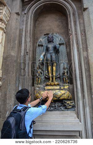 A young man praying at Mahabodhi Temple in Bodh Gaya, India.