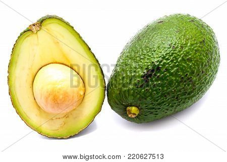 One whole avocado (Persea americana, alligator pear) and its half with a stone isolated on white background