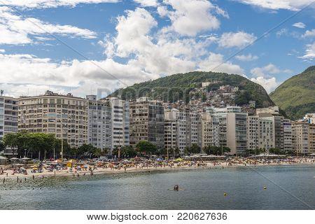 Rio de Janeiro, Brazil - January 3rd, 2018: Stand Up Paddle on Copacabana Beach, Rio de Janeiro, Brazil with buildings and a favela in background