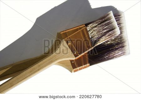 Two large synthetic high quality paint brushes sitting on a paint tin with a white isolated background.