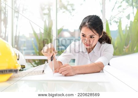 Female architecture in office using compasses to draw a architects project in paper