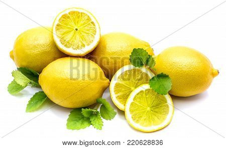 Composition of whole lemons and its slices on fresh green lemon balm leaves isolated on white background