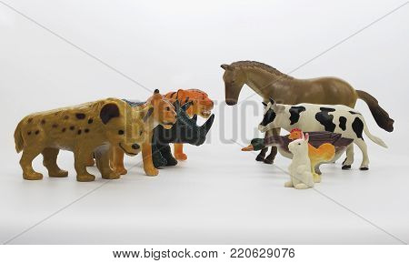 Animals: wild vs domestic. Isolated wild animals standing opposite to domestic animals toys.