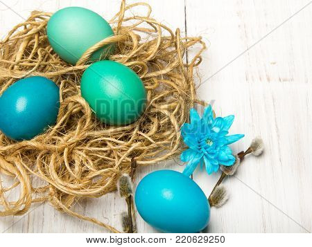 Easter background with eggs, nest and catkins on white wooden background, copy space