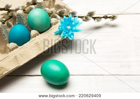 Easter background with eggs and catkins on white wooden background, copy space