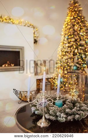 Cozy winter christmas interior with candles, fireplace and Christmas tree. Toning image, athmosphere of miracle and fairy tale. New year tree decorated with lightning garland. New year miracle.