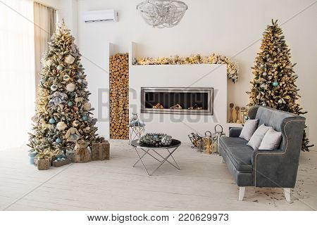 Cozy winter christmas interior. Christmas decoration of stylish living room with fireplace and Christmas tree. Classic white christmas interior background, empty room.