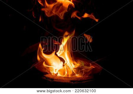 Fire close-up and red orange yellow color detail texture and abstract shape on black background.Fire flame on black background.