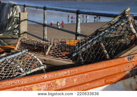 Lobster pots in a weathered orange boat with the coastline in the background