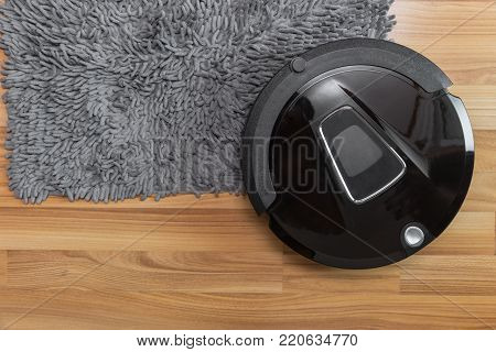 Robot vacuum cleaner on laminate wood floor with carpet cleaning