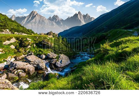 stream among the rocks in grassy valley. gorgeous summertime composite landscape with High Tatra mountain ridge in a distance