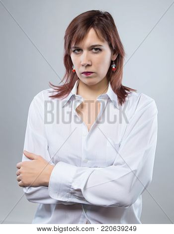 Skeptical woman with arms crossed on gray background