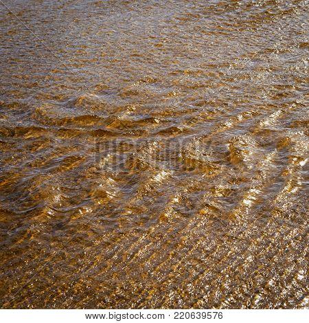 Sunlight on running tannin water ripple background