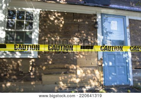 house fenced with a caution tape. the entrance to the house closed with the yellow tape