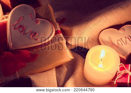 Warm and cozy winter with candles, gifts and ginger snap in the shape of heart. Still life for St. Valentine's Day