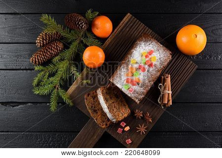 Flatlay of tasty homemade fruit cake with candied fruits, clementines, star anise, cinnamon and fir branch on black background overhead view