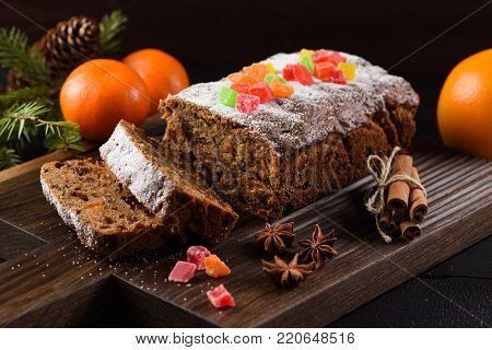 Traditional sliced freshly baked fruit cake decorated with candied fruits, star anise, cinnamon and clementines on dark background closeup