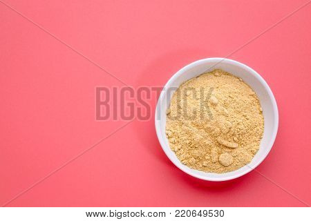 maca root powder in a lsmall ceramic bowl against pink background