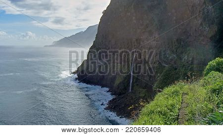The fascinating rocky coast of Madeira with a beautiful panoramic view over the waters of the Atlantic Ocean, the clouds and the high cliffs