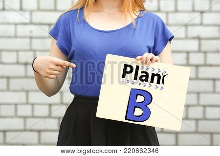 plan b. concept.device in blue near a brick wall. holds a wooden tablet and points at it with his finger. horizontal orientation