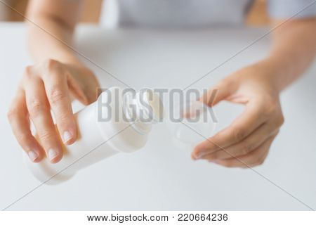 healthcare, people and medicine concept - woman pouring medication or antipyretic syrup from bottle to cup