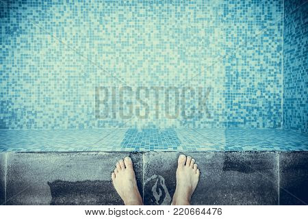 Selfie the feet at the pool side or edge with blue mosaic tiles at the bottom of the swimming pool. vintage tone.