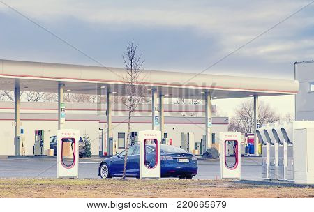 Olomouc Czech Republic December 31st 2017 - Tesla model S car being charged at Tesla charging station with gas station in background.