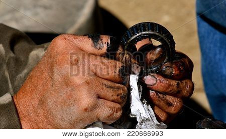 Fingers filled with grease clean a ball bearing from a wheel and axle connection