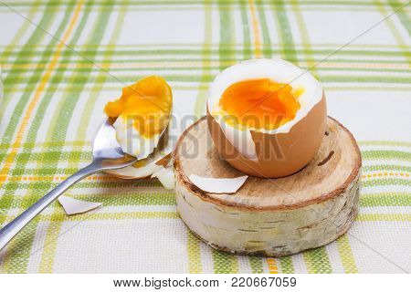 Boiled fresh smash broken egg for the breakfast on the wooden birch stand for eggs. Broken beige hen egg and pieces of shells, bright liquid orange yolk in the spoon. Messthetics aesthetic concept