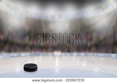 Low angle view of ice hockey puck on ice with deliberate shallow depth of field on brightly lit stadium background and copy space.