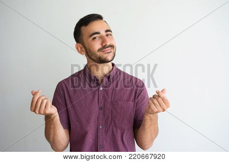 Closeup portrait of content man looking at camera, showing money gesture and asking for money. Money concept. Isolated front view on white background.