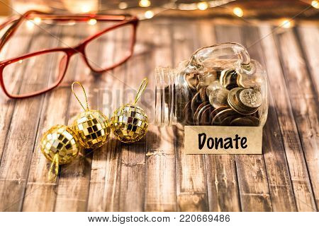 Donate money jar savings plan and giving motivational concept on wooden board