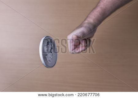 Flipping a silver coin in the air. A conceptual image of flipping a Canadian silver coin up in the air.