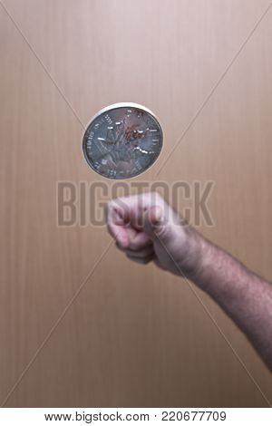Is it heads or tails? A conceptual image of flipping a Canadian silver coin up in the air.