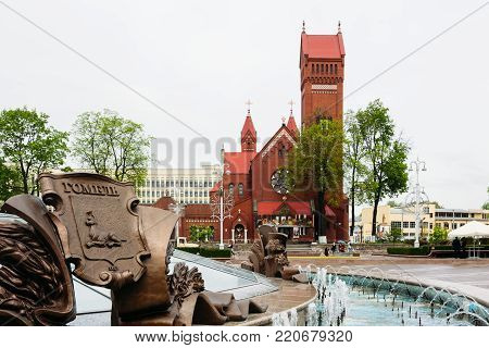 Minsk, Belarus - May 18, 2017: Fountain on the Independence Square in Minsk on the background of the red cathedral of St. Simon and Helena of the Catholic Church
