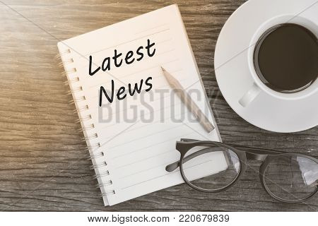 Latest news word with notebook with glasses, pencil and coffee cup on wooden table.