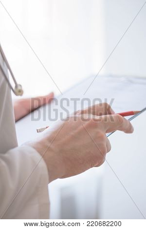 Close Up Of Hand Male Doctor Filling The Medical Form. Close-up Of Male Doctor Filling The Medical F
