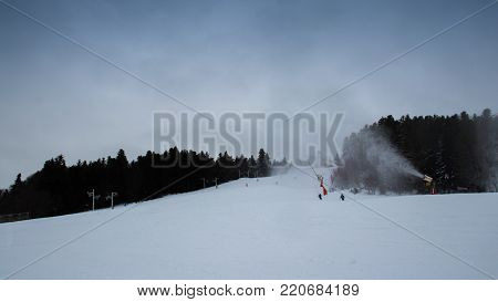 Snowmaking on ski slopes by snow cannon.People are engaged in mountain skiing and snowboarding on the ski track on the mountainside snow cannon