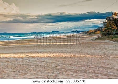 The evening sun shines on the beach at Gold Coast, Queensland, Australia. People are taking an evening walk at the beach before dinner.