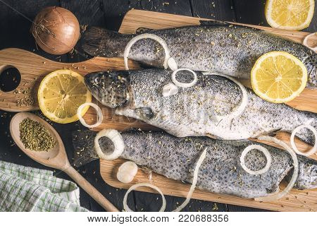 Fresh fish with onion and lemons on a trencher - Close-up with fresh trout, sprinkled with herbs, spices, onion rings and slices of lemon, placed on a wooden cutting board, on a vintage table.