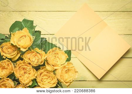 Roses bouquet and a blank message card - Greeting card idea with a beautiful bouquet of yellow roses and a blank message card with place for text, displayed on a yellow wooden background.