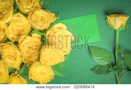 Yellow roses and a green envelope - Big bouquet of yellow roses and a single one, placed near a  closed letter, on a green wooden background. A greeting card idea or a birthday gift.