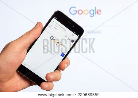 Adygea, Russia - January 4, 2018: the home page of popular web site the American search engine Google on the screen of the Chinese Xiaomi smartphone in male hand